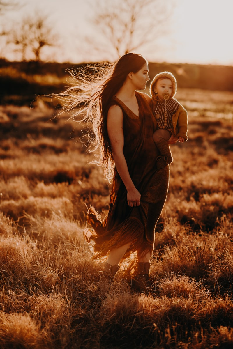 Bay Area Family Photography, mother standing with baby on her hip in a grassy field