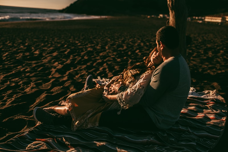 Bay Area Maternity Photography, couple sitting in the sand at sunset