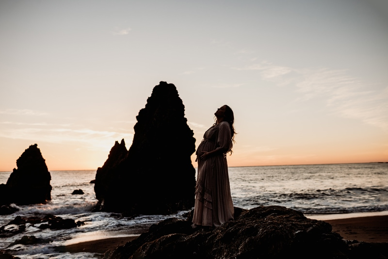 Bay Area Maternity Photography, woman standing on rock with sunset in the background