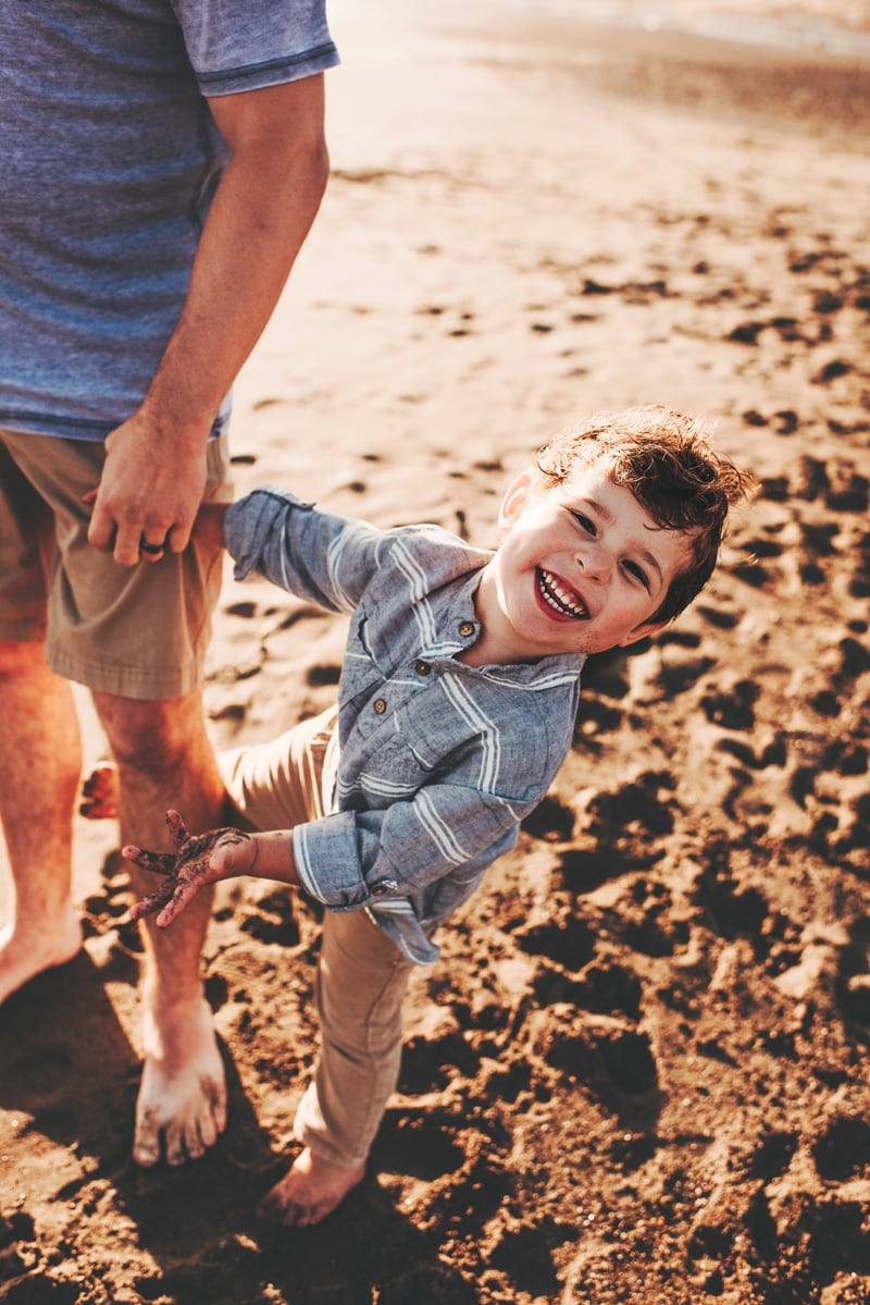 Bay Area Family Photography, little boy smiling while holding dad's hand at the beach