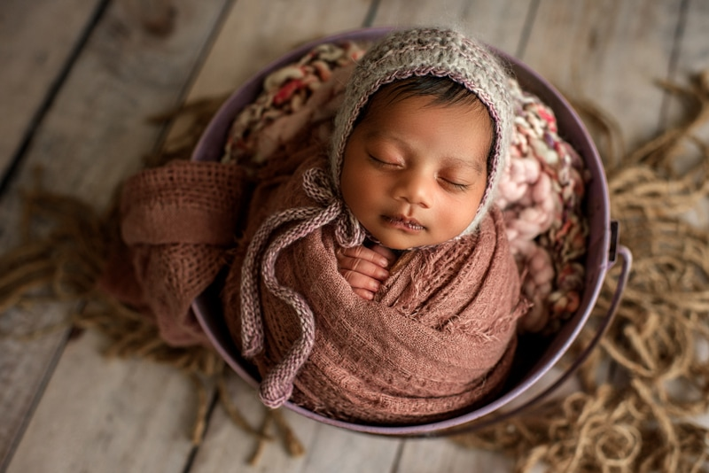 Bay Area Newborn Photography, baby in knit bonnet wrapped up in a basket