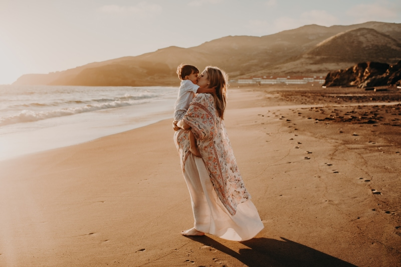 Bay Area Maternity Photography, mother holding little boy up for a kiss at the beach