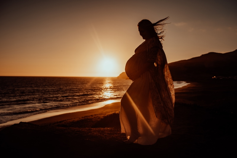 Bay Area Maternity Photography, mother standing at the beach with sunset behind her